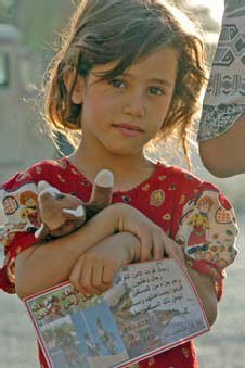 An Iraqi girl holds a Beanie Baby and a handbill given to her by Iraqi soldiers from the 1st Battalion, 4th Public Order Brigade during Operation Thunder Goodwill Aug. 17. Photo by U.S. Army Spc. David Kobi, 55th Signal Company