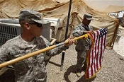 U.S. soldiers fold their national flag as they prepare to hand over their base to Iraqi forces in Iraq's southern province of Basra