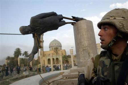 A U.S. soldier watches as a statue of Iraq's President Saddam Hussein falls in central Baghdad April 9, 2003. REUTERS/Goran Tomasevic