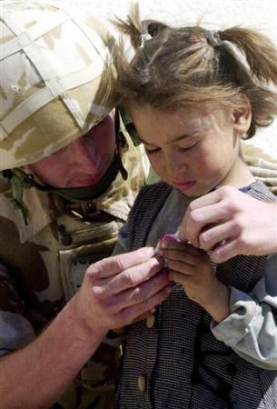 David Toughill, a soldier with Britain's 7th Armoured Brigade (Desert Rats), gives a boiled sweet to a local girl in Zubayr, southern Iraq, April 2, 2003. REUTERS/POOL/Tony Nicoletti-Daily Record