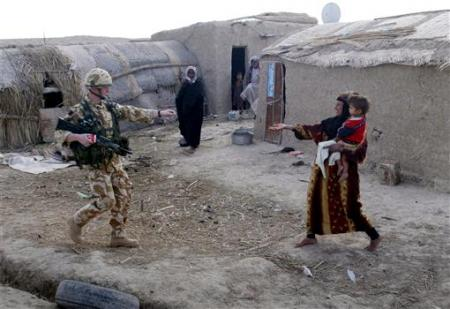 A British soldier from the Welsh Guards hands out candy to an Iraqi woman carrying her child during a patrol along the Glory Canal, 50 kms (32 miles) south of the town of Amara in southern Iraq, February 7, 2005. REUTERS/Bob Strong