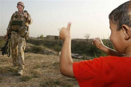 An Iraqi boy exchanges thumbs-up with a British soldier on patrol a few miles to the north of Basra July 12, 2007. REUTERS/Atef Hassan