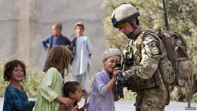 A British soldier shows his rifle to Afghan children during a patrol near the town of Lashkar Gah in Helmand Province. Most U.S. and British troops will be leaving the province by the end of 2014.
