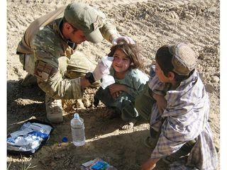 Lance Corporal Craig Murfitt gives first aid to an Afghan girl  [Picture: Crown Copyright/MOD 2010]
