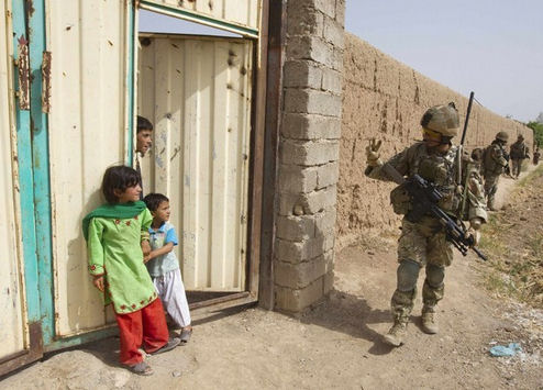 A British Army soldier of the 2nd Battalion, The Royal Gurkha Rifles waves to Afghan children during a patrol outside Patrol Base Chilli near the town of Lashkar Gah in Helmand province, southern Afghanistan, July 14, 2011. Picture taken July 14, 2011