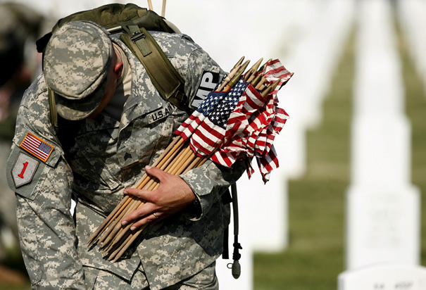 Soldier placing flags on graves