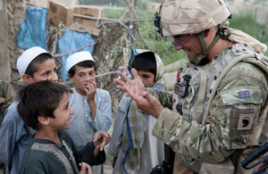 A British soldier chatting to Afghan children during a joint patrol with the Afghan National Police and Afghan National Civil Order Police in the Bolan area [Picture: Corporal Gary Kendall RLC, Crown Copyright/MOD 2010]
