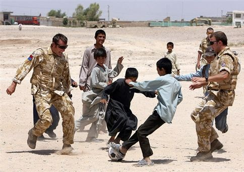 British soldiers playing football with children in Lashkar Gah, Afghanistan.