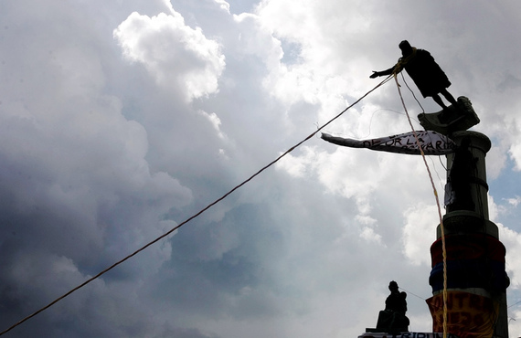 Venezuelan demonstrators use ropes to topple a Christopher Columbus statue in Caracas.
