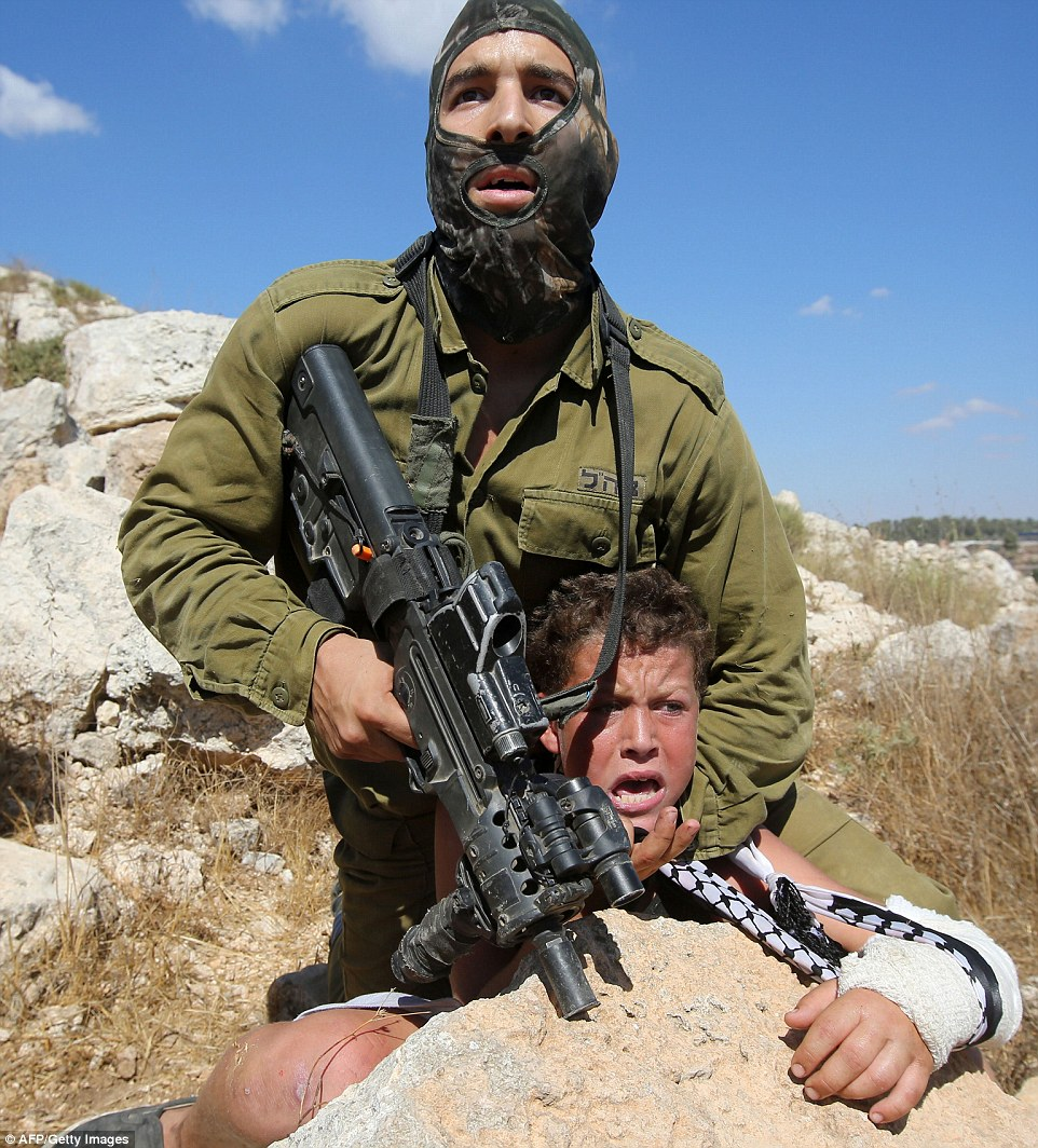 2BBD799300000578-3214441-Terrified_An_Israeli_soldier_puts_a_young_boy_in_a_headlock_at_g-a-22_1440789212168
