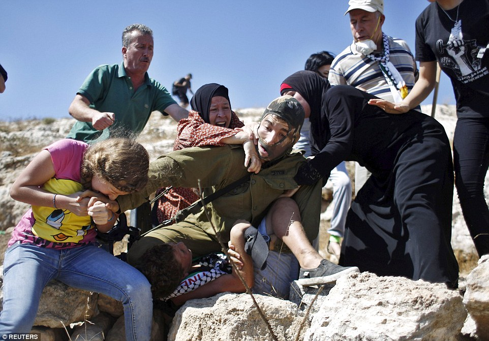 2BBEAFEB00000578-3214441-Palestinians_scuffle_with_an_Israeli_soldier_as_they_try_to_prev-a-20_1440789212166