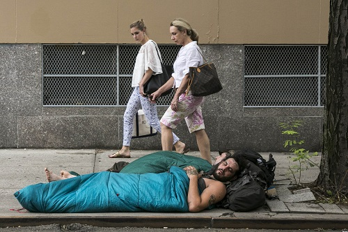 Women pass homeless people camped on 6th Street next to a Cooper Union building, Thursday, July 30, 2015. (Photo Credit: Natan Dvir)