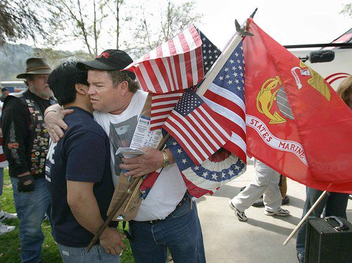 March 9, 2007 Gold Star Dad Mark Crowley, center, hugs a supporter [*ahem*] after a rally to support U.S. troops. Wearing a t-shirt with an image of his son, killed while serving in Iraq, Crowley accepts dozens of flags to bring with him to Washington D.C. (Spencer Weiner / LAT)