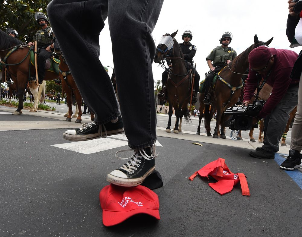 Mark Ralston/AFP via Getty A Trump protester stomps on a Make America Great Again hat
